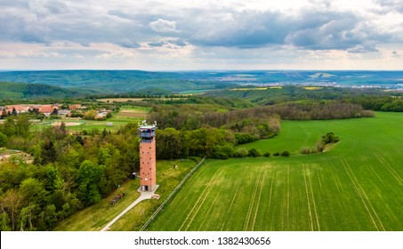 """Aerial shot of lookout tower in Hlina village, czech republic. Wooden building has name of """"Vladimir Mensik"""" which was famous czech actor. Rainy day, green field in foreground, gray clouds."""