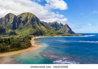 Aerial shot off the coast over Tunnels beach on Hawaiian island of Kauai with Na Pali mountains behind