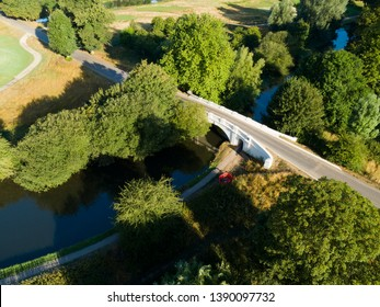 Aerial shot of old bridge over Grand Union Canal waterway, United Kingdom.