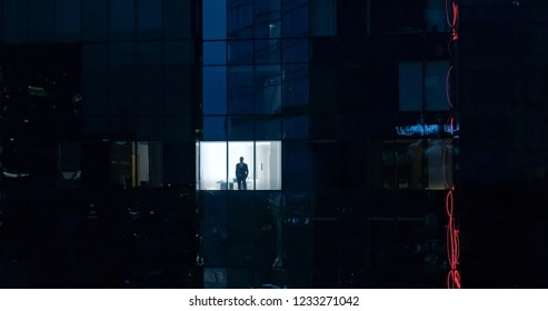Aerial Shot: From Outside into Office Building with Businessman Looking out of the Window. Beautiful Shot of The Financial Business District Skyscrapers in the Evening.