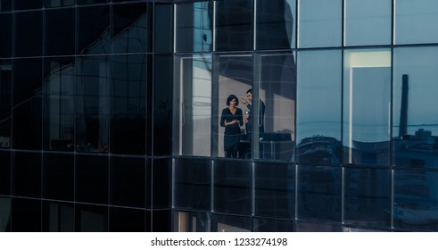 Aerial Shot From Outside of the Skyscraper: Businessman and Businesswoman Talking Business while Standing by the Office Window. Shot of the Financial Business District and Businesspeople Working