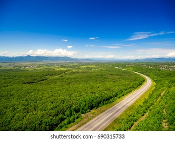 Aerial shot of road, forest and sky