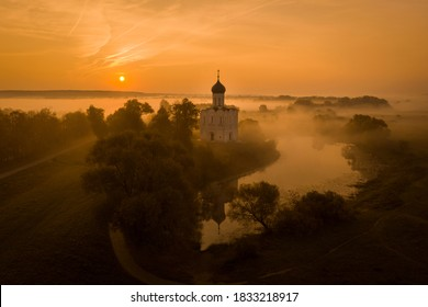 Aerial shot of a Russian Orthodox church above a misty field lit by the rising sun. A pond near the church, a river in the background. No people.