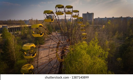 Aerial shot of a rusty Ferris wheel in Chernobyl zone with abandoned houses in spring