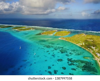 aerial shot of sailboats in a pristine tropical atoll near a village