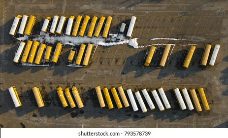 Aerial shot of school busses parked in a lot.