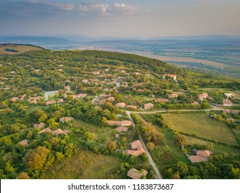 Aerial shot of a small mountain village in Bulgaria - typical rural scenery, beautiful sunrise