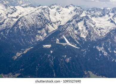 aerial shot, from a small plane, of glider plane flying high in mountain valley with slopes covered with firs and snow , shot on a bright springtime day near Tonale pass,   Alps , Italy