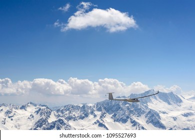 aerial shot, from a small plane, of glider plane flying high in the valley north of Presanella range , shot on a bright springtime day in  Alps , Italy