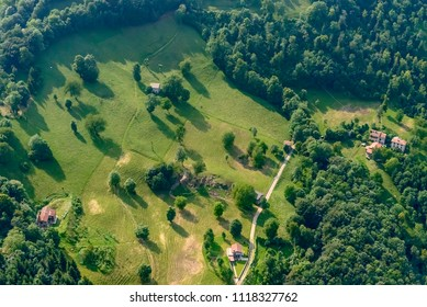aerial shot, from a small plane, of green meadows and trees on Orobie slopes, shot on a bright late springtime day near Gerosa, Orobie, Bergamo, Lombardy, Italy