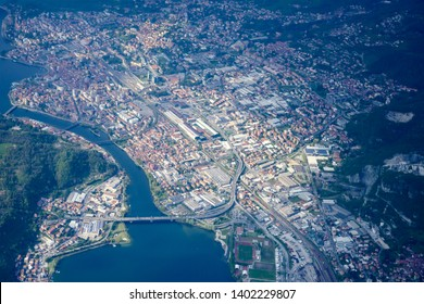 aerial shot, from a small plane, of industrial and historical town on banks of Adda river coming out of Lario lake, shot on a bright springtime day at Lecco, Lombardy, Italy
