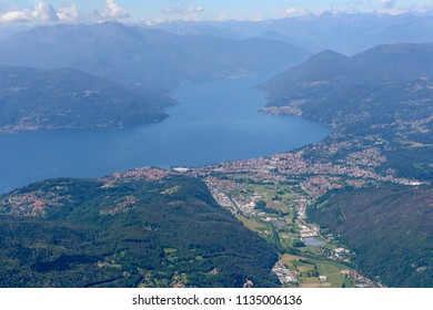 aerial shot, from a small plane, of Luino village and Maggiore lake , shot on a bright early summer day from above Valtravaglia valley, Varese, Verbano, Lombardy, Italy