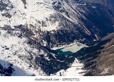 aerial shot, from a small plane, of melting ice and late spring snow on Scais lake, shot on a bright springtime day in Orobie mountains, Bergamo , Italy