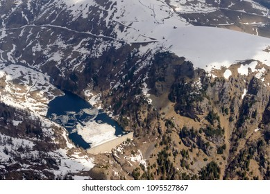 aerial shot, from a small plane, of melting ice and late spring snow on San Marco lake, shot on a bright springtime day in Orobie mountains, Bergamo , Italy