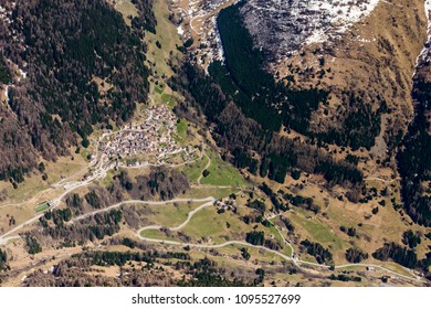 aerial shot, from a small plane, of Pezzo mountain village in Messi valley , shot on a bright springtime day in  Alps ,  Lombardy , Italy
