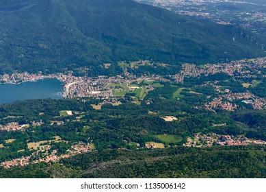 aerial shot, from a small plane, of Porto Ceresio touristic village on Lugano lake and nearby Besano village , shot on a bright early summer day, Varese,  Lombardy, Italy