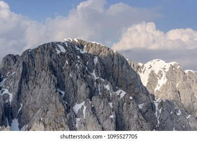 aerial shot, from a small plane, of Presolana peak range steep cliffs shot in Orobie mountains in bright springtime light, Bergamo , Italy