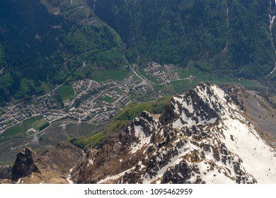 aerial shot, from a small plane, of Valbondione mountain village under steep cliffs of Coca peak, shot on a bright springtime day in Orobie, Bergamo,  Lombardy , Italy