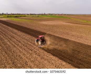 Aerial shot of a tractor cultivating field at spring