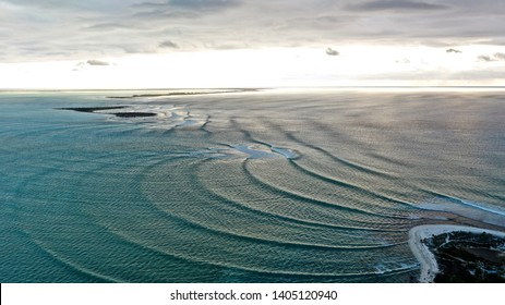 Aerial shot of waves spreading out as they approach tropical lagoon at sunset