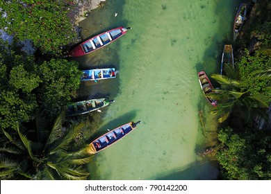 Aerial shot of White River, Ochios Rios, Jamaica with 4 colorful fishing boat moored in a small fishing settlement. Fishes are visible through the clear waters.