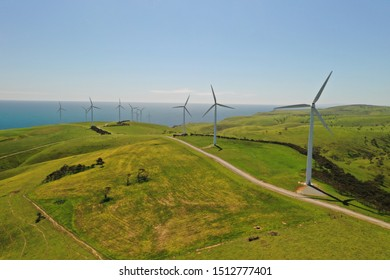 Aerial shot of wind mills rotating by the force of the wind and generating renewable energy in a green ecologic way to the planet on a background of seaside on sunny day.