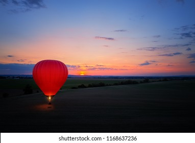 Aerial, side view of the evening landing of shining red-blue hot air balloon against sunset. Red hot air balloon firing its burner lighting up the entire balloon against  colorful evening landscape.