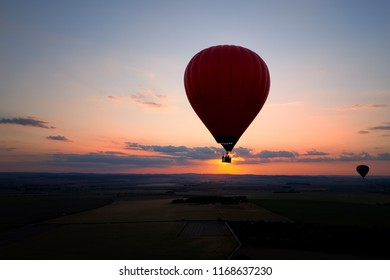 Aerial, side view of the silhouette of red hot air balloon directly against sunset. Two hot air balloons in the colorful evening landscape.