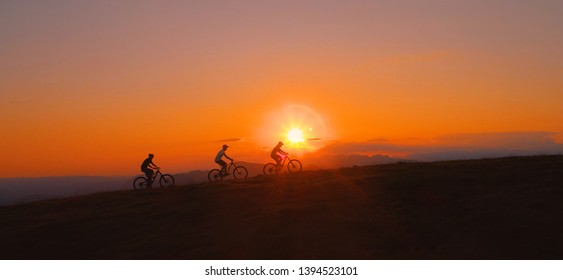 AERIAL, SILHOUETTE, LENS FLARE: Breathtaking evening sunbeams shine on the tourists riding ebikes in the scenic nature. Three downhill bikers pedalling their bicycles up along grassy hill at sunrise.
