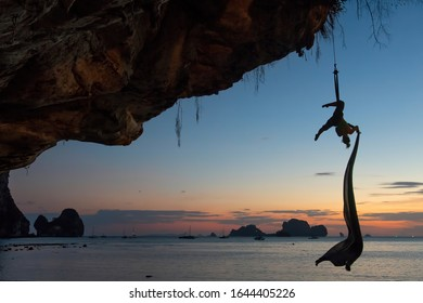 Aerial silk performance on the sunset Tonsai beach (unique place thanks to the rock climbing community). Krabi province, Thailand.