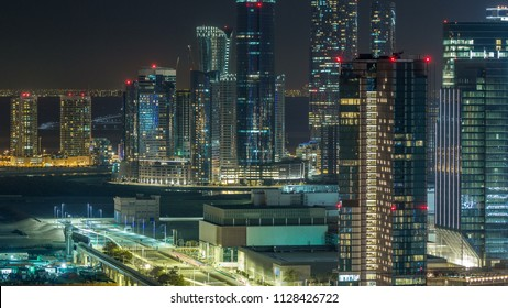 Aerial skyline of Abu Dhabi city centre from above night timelapse with illuminated skyscrapers.