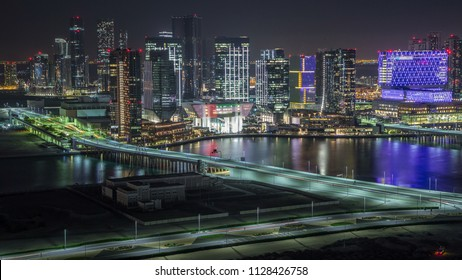Aerial skyline of Abu Dhabi city centre from above night timelapse with illuminated skyscrapers with bridge and traffic on a road