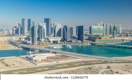 Aerial skyline of Abu Dhabi city centre from above timelapse before sunset with shadows from skyscrapers.