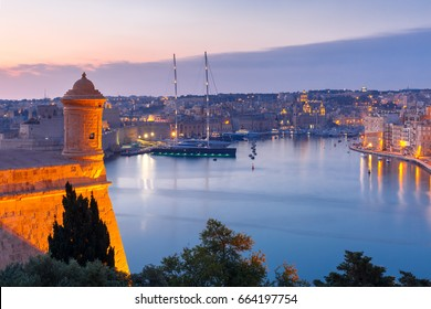 Aerial skyline view of Birgu and Grand Harbor with ships, as seen from Valletta during morning blue hour, Malta.