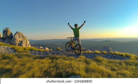 AERIAL: Smiling extreme cross country biker celebrates reaching top of the scenic hill towering above the picturesque evening nature in Slovenia. Young man victoriously pumping his fists at sunset.