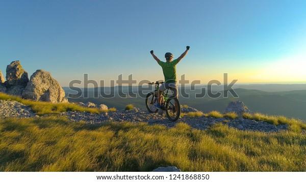 AÉRIEN: Souriant, le motard de fond célèbre son arrivée au sommet de la colline pittoresque qui s'élève au-dessus de la nature pittoresque du soir en Slovénie. Jeune homme qui, par procuration, se tire les poings au coucher du soleil.
