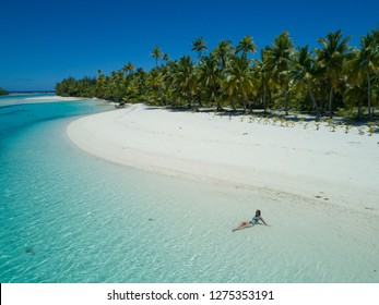 AERIAL SPEED UP: Young woman relaxing in the glassy ocean water by the lush exotic island. Relaxed female traveler enjoying her summer holiday on One Foot Island by floating in shallow ocean water.