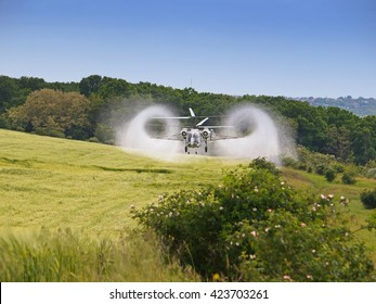 Aerial spraying over a field of wheat