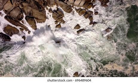 Aerial of storm waves breaking onto rocks