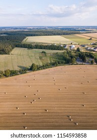 Aerial: stubble field with straw bales at late summer. Polish landscape from drone.