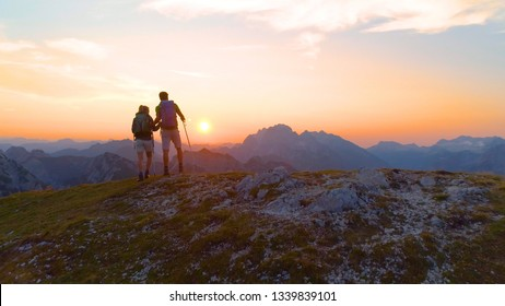 AERIAL, SUN FLARE: Unrecognizable hiker couple observes the breathtaking evening landscape from the mountaintop. Sporty young man and woman watches the sunrise from a peak in the serene Julian Alps.