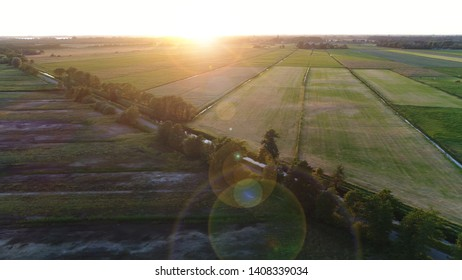 Aerial sundown photo of rural area or countryside is a geographic zone that is located outside towns and cities showing both naturals as agricultural areas and sunflare rings over lens