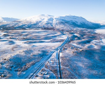 Aerial sunny winter view of Abisko National Park, Kiruna Municipality, Lapland, Norrbotten County, Sweden, shot from drone, with road and mountains
