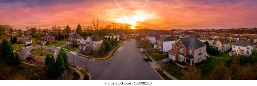 Aerial sunset panorama view of luxury upscale residential neighborhood gated community street in Maryland USA, American real estate with single family homes brick facade colorful sky cul-de-sac