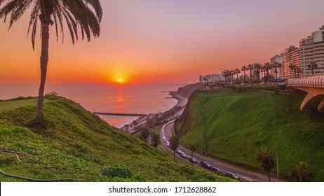 Aerial sunset view of Lima's Coastline in the neighborhood of Miraflores view with orange light, Lima, Peru. Road with traffic and beach with ocean. Palm near Love park