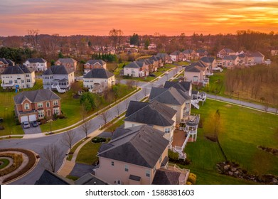 Aerial sunset view of luxury upscale residential neighborhood gated community street in Maryland USA, American real estate with single family homes brick facade colorful sky