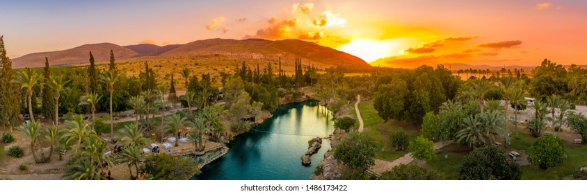 Aerial sunset view of the popular summer destination park Sachne or Gan Hashlosha with turquoise water and palm trees in Israel