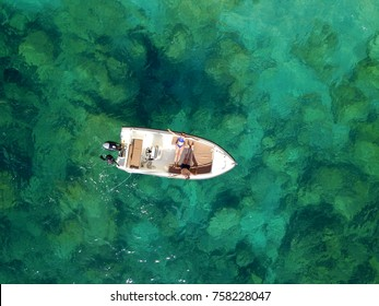 Aerial survey of a happy couple on a boat sunbathe together on a warm summer day