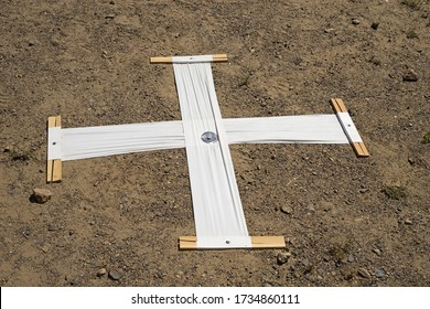 aerial survey marker consisting of a white plastic cross nailed to the ground to show up in aerial photos