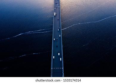 Aerial of Tasman bridge over wide flowing Derwent river in Tasmania Australia, with traffic, cars and trucks, crossing at sunset.